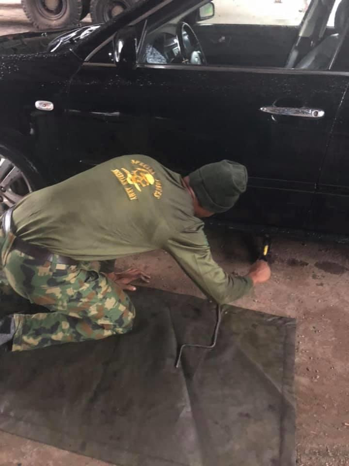 PHOTOS: Soldier appreciated by Nigerian man after helping him to repair his faulty car in the rain